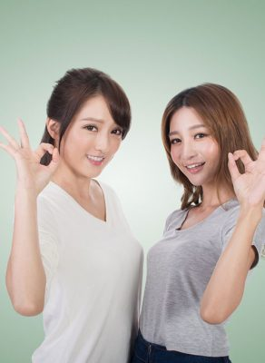 """Two young Asian woman standing next to each other, looking at the camera and giving the """"okay"""" gesture with their hand."""