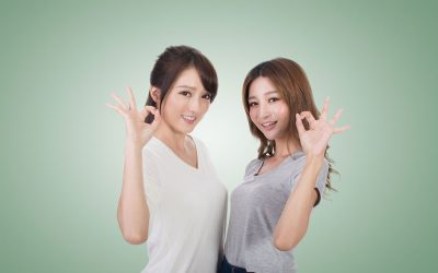 "Two young Asian woman standing next to each other, looking at the camera and giving the ""okay"" gesture with their hand."