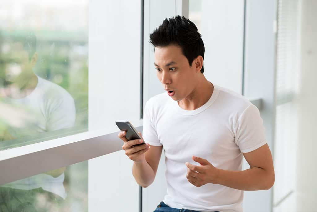 A young Asian man looking at his phone with a surprised look on his face. He is standing next to a window, and a blurred out green background can be seen.