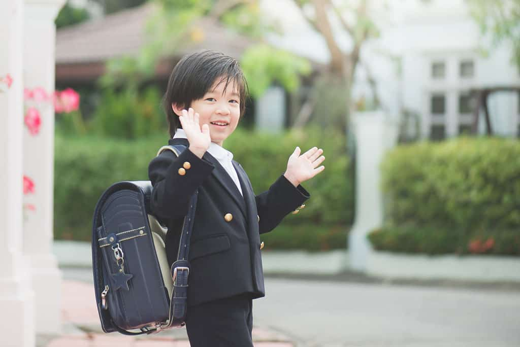 A young, Asian boy dressed in a Japanese school uniform and backpack, waving goodbye.