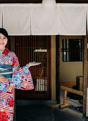 An Asian woman dressed in a Japanese kimono standing in front of a Japanese style entrance, with her hands gesturing to the entrance to welcome someone.