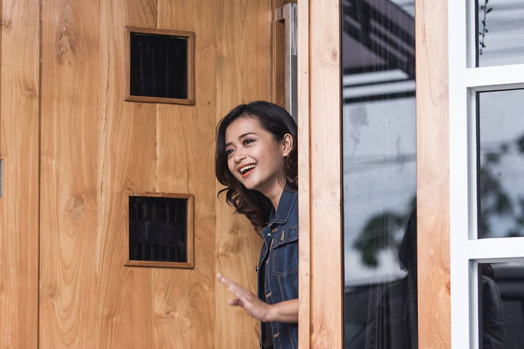 An Asian woman looking out of a door of a home, waving goodbye to someone.