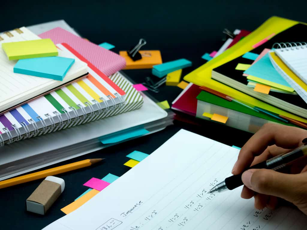 A stack of note books, color sticky note tabs, and an open notebook with Japanese written on it. On this open notebook, we can see a hand holding a pen, as if in the process of writing more.