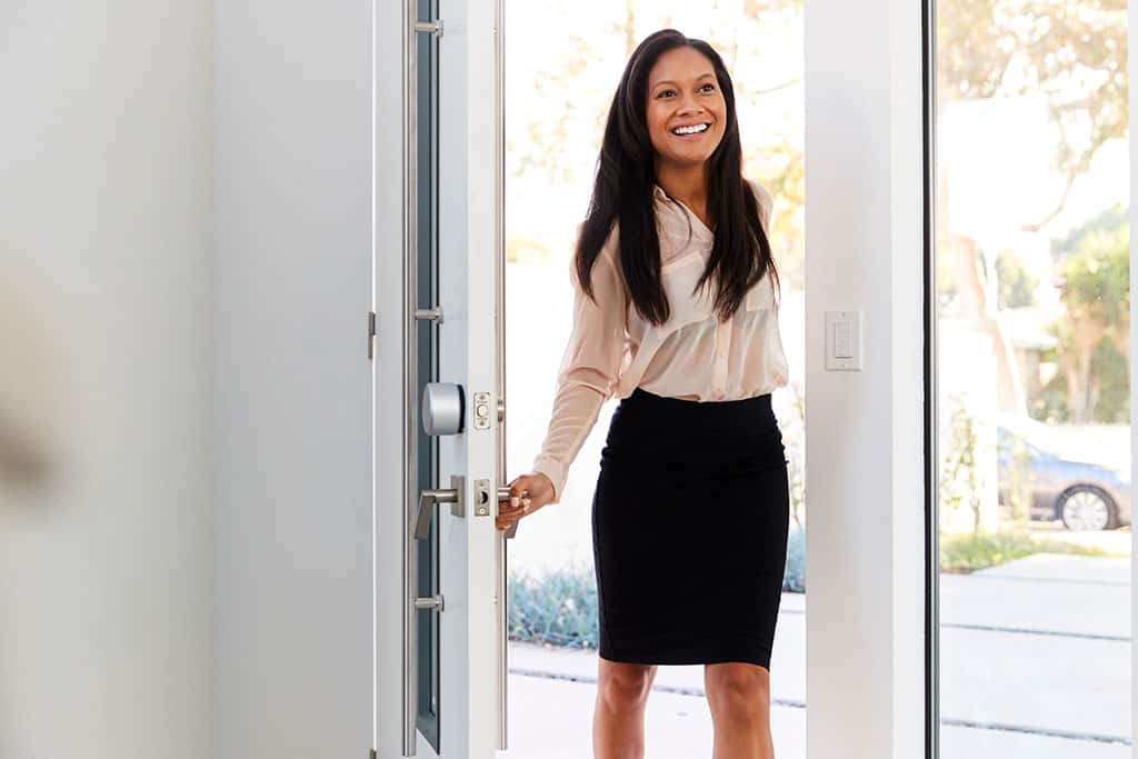A young, Asian woman is smiling, dressed in business attire, opening the front door of a home, walking in as if coming home from work.