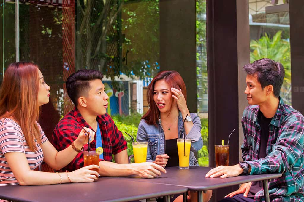 A group of young Asian men  (2) and woman (2) sitting down at a table drinking iced tea and juice, having a conversation.
