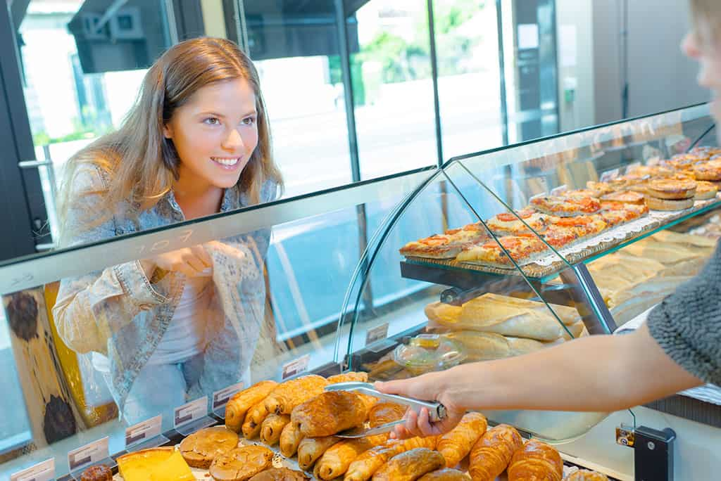 A young woman standing in front of a display case filled with pastries. She is pointing to a pastry and the arm of a store employee can be seen taking the item with a pair of tongs.