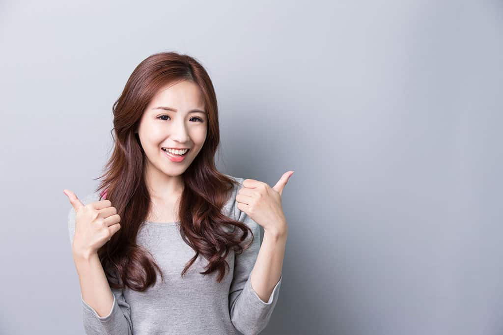 A young Asian woman wearing a grey shirt giving two thumbs up with her hands.