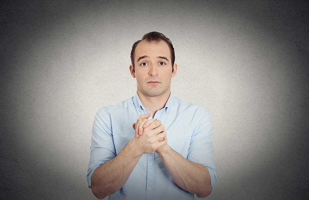 A middle aged man clasping his hands together with his facial expression looking as if he is asking for a favor.