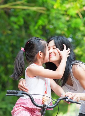 A young girl on a bicycle being held by her mom. She is kissing her mom on the cheek.