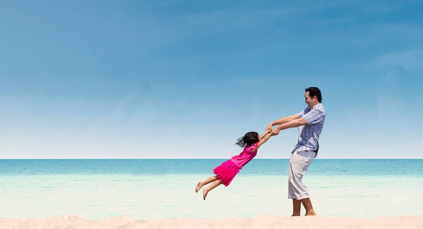 A young man swinging a young girl by her arms on the beach.