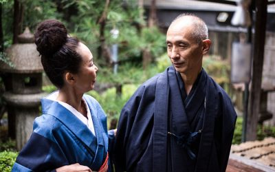 An older woman and man dressed in traditional Japanese clothes, outside in a garden looking at one another.