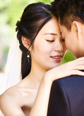 An close-up of a young, Asian couple. The man is seen from the back, while the woman is wrapping her arms around his neck, embracing him. They are touching one another with their foreheads. The woman appears to be wearing a white veil.