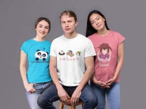 Two young woman and a young man. The young women are wearing a shirt with an illustration of a panda on one, and on the other, an illustration of a girl. The man sitting in the middle has a white shirt with cute sushi character illustrations on it.