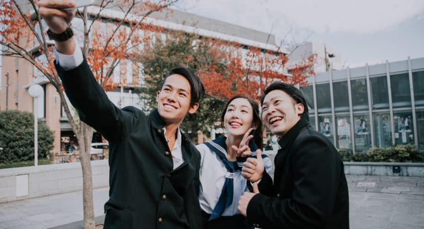 Two young Asian boys, and one young Asian girl, all wearing Japanese high school student uniforms. The boy on the left is holding up a smartphone to take a selfie of them all together.
