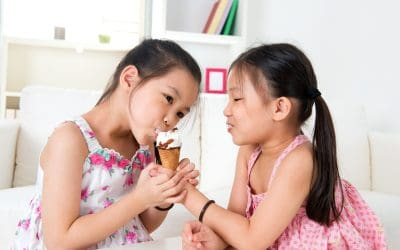 Two young girls in a white room sharing an ice cream cone.