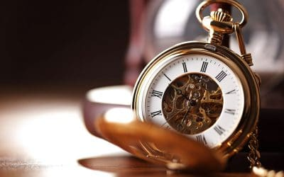 A gold, open pocket watch with its face visible is resting on a tabletop with the background blurred.
