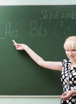 """A young, blonde woman in front of a blackboard pointing at the """"ABCs"""" written on it with a piece of chalk."""