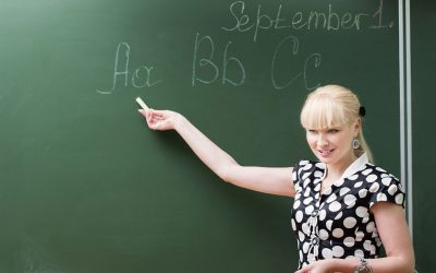 "A young, blonde woman in front of a blackboard pointing at the ""ABCs"" written on it with a piece of chalk."