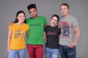 """A woman on the left wearing a shirt with Japanese food, next to her a young man with a green shirt with Japanese text, to the right of him a girl with black shirt with the word """"Kawaii"""" on it, and to the right, a young man wearing a grey shirt with a Japanese warrior illustration on it."""
