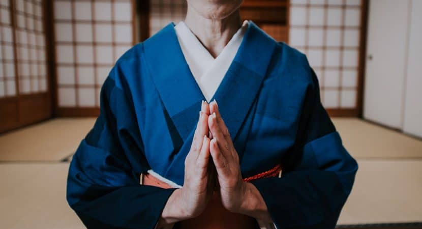 A woman dressed in traditional Japanese clothes with her hands together as if in prayer or saying please.