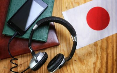 Items on a table: A small Japanese flag to the right, a brown and green book to the left, with a smartphone connected to a pair of headphones on top of it.