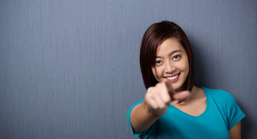 A young, Asian woman point straight at the camera and smiling.