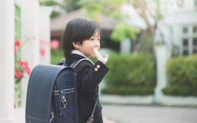 A young Asian boy dressed in a Japanese school uniform and backpack waving to someone.