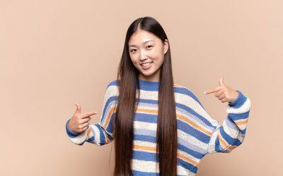 A young, Asian woman with a blue, white, and orange stripped shirt with both pointer fingers pointing to herself.