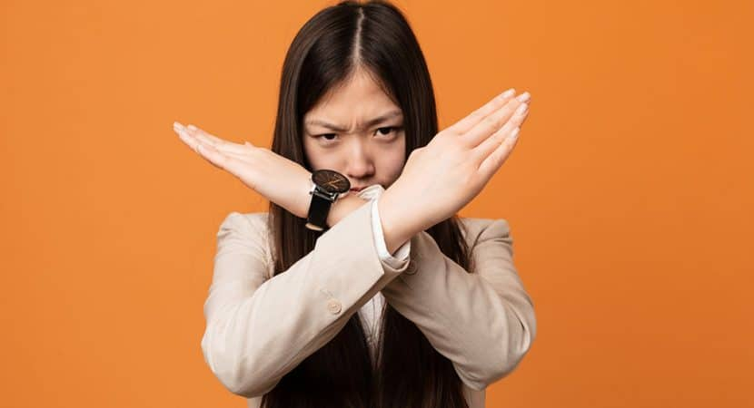 """A young, Asian woman with her arms crossed in front of her face to form an """"X"""" shape."""
