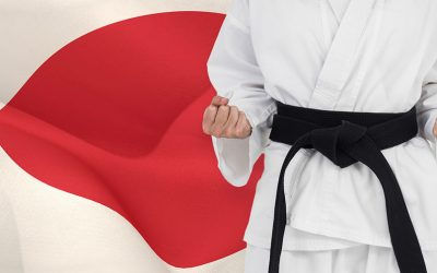 Someone wearing a white karate gi uniform with a black belt, standing in front of the flag of Japan.