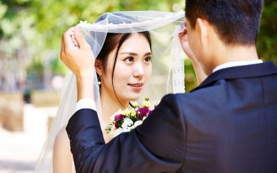 An Asian groom lifting up the bridal veil of the young Asian bride.