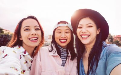 Three young girls standing next to each other and looking forward while taking a selfie.