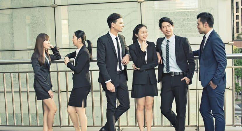A group of business people (4 men and 2 women) talking to each other. The two women are talking in one group, and the 4 men are talking in their own group.