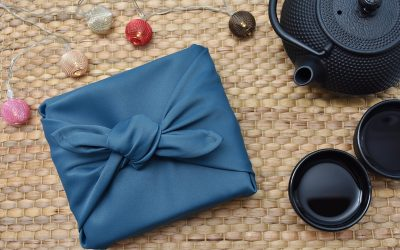 A box wrapped in a blue Furoshiki, or Japanese wrapping cloth on the left side, with an iron teapot and two cups to the right. There are also some Christmas looking ball decorations above the wrapped box.