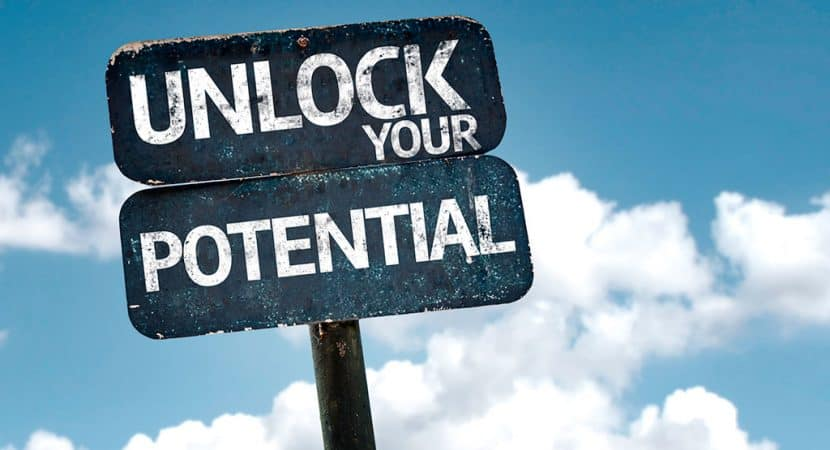 """A wooden sign with the words, """"UNLOCK YOUR POTENTIAL"""" written on it. The blue sky and white clouds is in the background."""