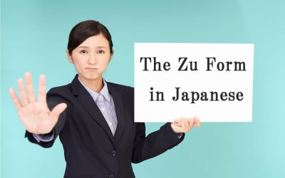 """A younger, Asian woman in a black business suit with her right hand out as if to say, """"stop."""" She is holding a white board that reads, """"The Zu Form in Japanese."""""""
