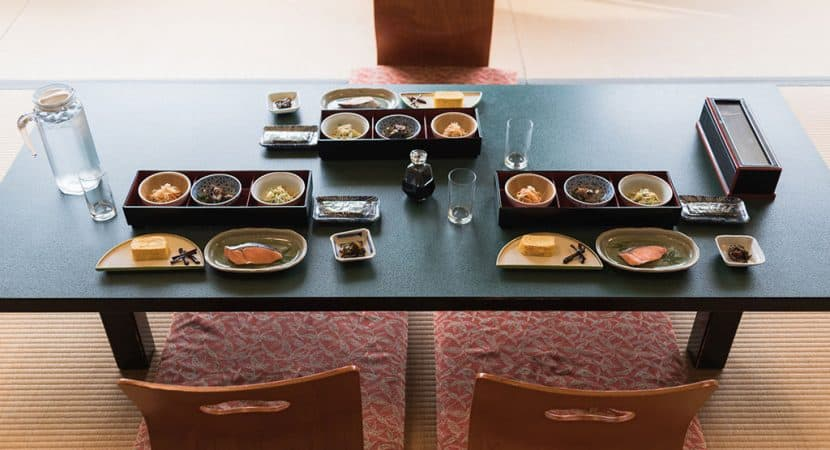 A low table in a tatami style Japanese room with chairs that sit directly on the ground. On the table are three meals made up a different dishes like salmon, egg, and assorted vegetables.