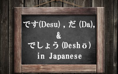 """A small blackboard with a wooden frame hanging on a wooden wall. The text in English reads, """"Desu, Da, & Desho in Japanese."""""""