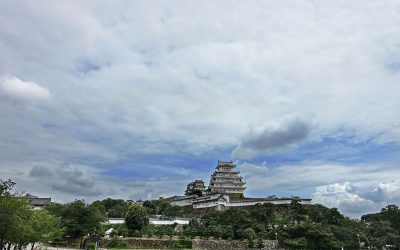 """The Himeji Castle seen from afar, with the surrounding landscape and sky visible all around. There is text in it that reads, """"The Sou Form in Japanese: It Looks Like ~ I Hear That ~"""""""