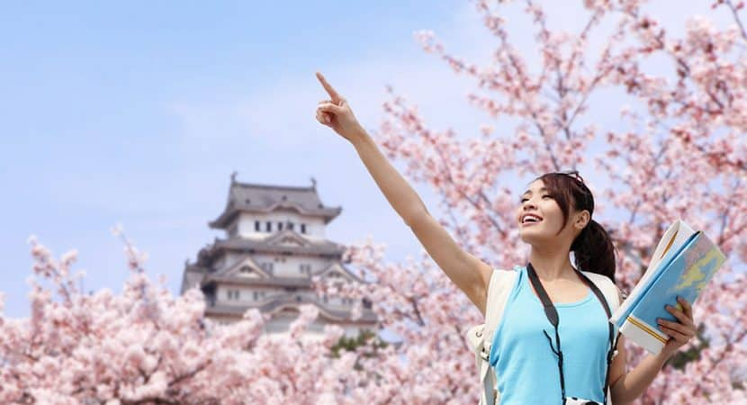 A young, Asian woman holding a map and pointing at something to the left off in the distance. Behind her are many blossoming cherry blossom cherries with pink flowers and a Japanese castle.