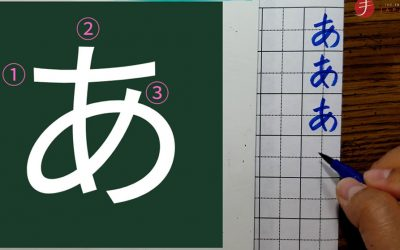 """A screenshot of the Japanese hiragana character """"a"""" with the stroke order. Next to it on the right, someone's had is seen writing it in on a piece of paper three times in blue ink."""