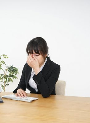 A young, Asian businesswoman at her desk pinching the bridge of her nose while looking very tired.
