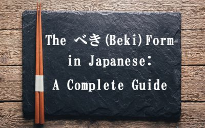 """A black, stone-like plate on a wooden tabletop. There is a pair of chopsticks on the left side of the plate. The text on this image reads, """"The Beki Form in Japanese: A Complete Guide"""""""