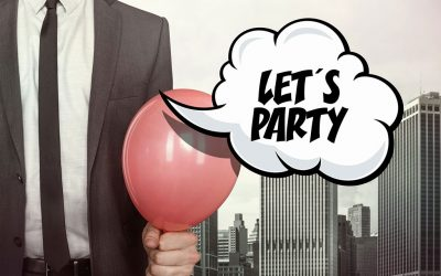 """An image of a man (only his torso is visable) wearing a suit and tie holding a red balloon. There are buildings in the background and a comic speech bubble that has text that reads, """"LET'S PARTY"""""""