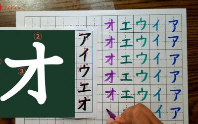 """The katakana character """"o"""" is shown on the left side of the image. On the right, a girl's hand can be seen writing the katakana characters """"a, i, u, e, o"""" in different colors of ink with a pen on the right."""