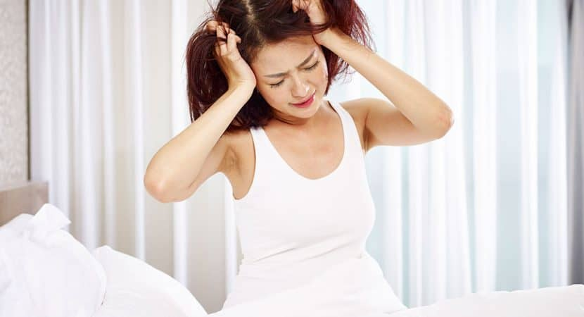 An Asian woman wearing a white tank-top sitting up in her bed with both her hands grabbing her hair, as if resenting getting up or is frustrated.