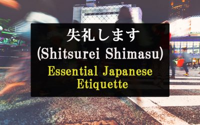 """In the background, people can be seen crossing the street with a crosswalk in what appears to be Tokyo, but they are blurry. The foreground as text that reads, """"Shitsurei Shimasu Essential Japanese Etiquette."""""""