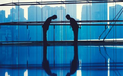 Silhouettes of two men can be seen bowing towards each other. They are in a building with glass windows, and in the background, other tall buildings can be seen.