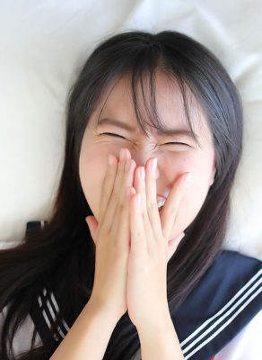 A young, Asian girl in a Japanese high school uniform lying down on a bed. Her hands are covering her mouth while she is laughing at something.